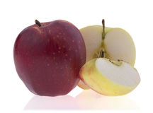 Tasty ripe apple lying next to sliced apples, isolated on Royalty Free Stock Photos