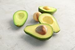 Tasty avocados cut into halves on light background. Tasty ripe avocados cut into halves on light background Royalty Free Stock Image