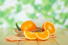 Tasty ripe oranges in basket. Tasty ripe oranges in wicker basket on wooden table Royalty Free Stock Photo