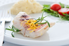 Tasty roast fish. Roast fish sprinkled with a lemon and rosemary Royalty Free Stock Image