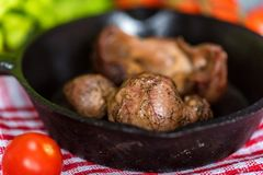 Tasty roasted chicken giblets in pan. Close up frying pan with delicious roasted chicken giblets on checkered cloth. Selective focus Stock Images