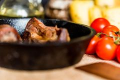 Tasty roasted chicken giblets in pan. Close up frying pan with delicious roasted chicken giblets with other food and wooden spatula in background. Selective Royalty Free Stock Photo
