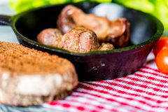 Tasty roasted chicken giblets in pan and rye bread. Close up frying pan with delicious roasted chicken giblets with rye bread and tomatoes on checkered cloth Royalty Free Stock Image