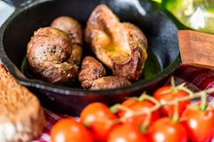 Tasty roasted chicken giblets in pan and rye bread. Close up frying pan with delicious roasted chicken giblets with rye bread and tomatoes. Selective focus Stock Photos