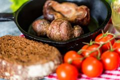 Tasty roasted chicken giblets in pan and rye bread. Close up frying pan with delicious roasted chicken giblets with rye bread and tomatoes. Selective focus Royalty Free Stock Photos