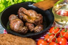 Tasty roasted chicken giblets in pan and rye bread. Close up frying pan with delicious roasted chicken giblets with rye bread and tomatoes. Selective focus Royalty Free Stock Photography