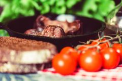 Tasty roasted chicken giblets in pan and rye bread. Close up frying pan with delicious roasted chicken giblets with rye bread and tomatoes. Selective focus Royalty Free Stock Image