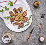Tasty roasted pieces of pork with mushroom sauce on a white plate with herbs and vintage cutlery wooden rustic background top v Stock Photo