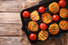 Tasty roasted potatoes and tomatoes with rosemary close up on a. Tasty roasted new potatoes and tomatoes with rosemary close up on a grill pan. horizontal view royalty free stock photo