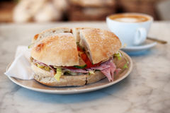 Tasty roll. This is an image of a tasty bread roll filled with ham, cheese, lettuce, cucumber, and tomato. Next to the roll is a cup of coffee which has stock image