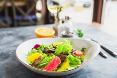 Tasty salad with citrus, lettuce and chicken liver with glass of vine. Healthy food stock images