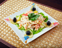 Tasty salad decorated with olives on skewers Royalty Free Stock Photo
