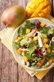 Tasty salad of grilled chicken breast, mango, arugula, lettuce a. Nd chicory close-up on the table. vertical view from above royalty free stock images