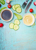 Tasty salad preparation with vinegar and mustard dressings and cutlery on light shabby chic blue background, top view. Place for text. Healthy eating or diet royalty free stock image