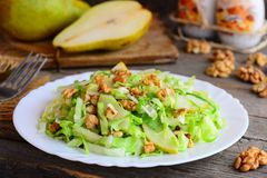 Quick pear and cabbage salad. Homemade salad with fresh pear, cabbage and walnuts on a white plate and on rustic wooden background Royalty Free Stock Images