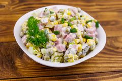 Tasty salad with sausage, green pea, canned corn, bell pepper, cucumber and mayonnaise on wooden table stock photography