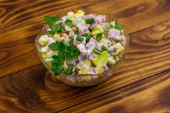 Tasty salad with sausage, green pea, canned corn, bell pepper, cucumber and mayonnaise on wooden table stock images