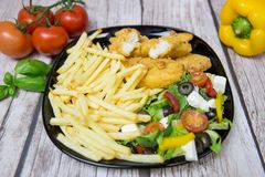 Tasty salad with stripes and frites royalty free stock photography