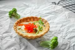 Tasty salmon tartlet on parchment. Closeup Stock Image