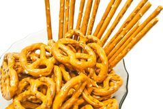 Tasty salted pretzels and breadsticks on a plate. Tasty salted pretzels and breadsticks on white Royalty Free Stock Photo