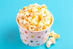 Tasty salty popcorn in paper cup on bright blue background royalty free stock photography
