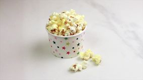 Tasty salty popcorn in paper cup on light marble background stock footage