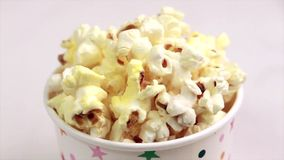 Tasty salty popcorn in paper cup on light marble background stock video