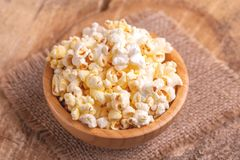 Tasty salty popcorn in wooden bowl on burlap napkin. Pastime watching movies. Cinema snacks. Copy space stock images
