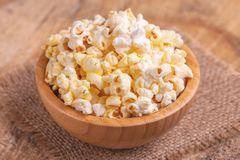 Tasty salty popcorn in wooden bowl on burlap napkin. Pastime watching movies. Cinema snacks. Copy space stock photography