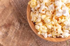 Tasty salty popcorn in wooden bowl on burlap napkin. Pastime watching movies. Cinema snacks. Copy space stock photos