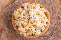 Tasty salty popcorn in wooden bowl on burlap napkin. Pastime watching movies. Cinema snacks. Copy space stock photo