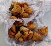 Tasty Samosas. A Click of Delicious Indian snack food Samosas with fried chillies unpacked from paper bag stock image