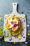 Tasty sandwich with avocado boiled eggs, pumpkin seed and edible viola flowers in a white board. healthy food Stock Photography