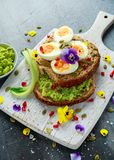 Tasty sandwich with avocado boiled eggs, pumpkin seed and edible viola flowers in a white board. healthy food Royalty Free Stock Photos