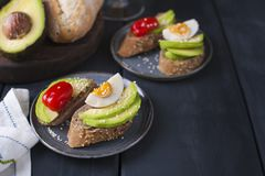 Tasty sandwich with avocado, tomato and poached egg on wooden chopping board, close up, selective focus. Healthy delicious royalty free stock photos