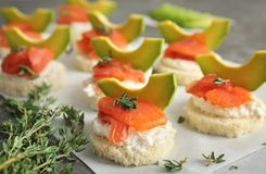 Tasty sandwiches with fresh sliced salmon fillet. And avocado on table, closeup stock photography