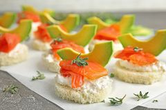 Tasty sandwiches with fresh sliced salmon fillet. And avocado on table, closeup royalty free stock photography