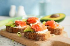 Tasty sandwiches with fresh sliced salmon fillet. And avocado on wooden board, closeup stock image