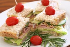 Tasty sandwiches on wholewheat bread. Tasty club sandwiches with green lettuce, grated cheese, smoked ham and wholegrain mustard on wholewheat bread with Stock Photo