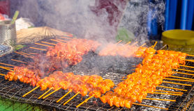 Tasty satay chicken. Cooking on a hot charcoal grill in Ramadan Bazaar during the holy month of Ramadan royalty free stock image