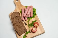 Tasty sausage and bread with lettuce and tomato for lunch and dinner royalty free stock photography