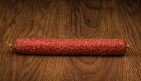 Tasty sausage i  on a wooden background Stock Images