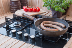 Tasty sausage in the pan on stove with vegetables Stock Photography