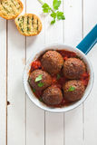 Tasty savory ground beef meatballs in tomato sauce stock images