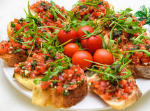 Tasty savory tomato Italian appetizers, or bruschetta, on slices of toasted baguette garnished with pesto and ruccola Stock Image
