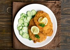 Schnitzel with cucumber salad. Tasty schnitzel with cucumber salad on plate over wooden table. Top view, flat lay royalty free stock image