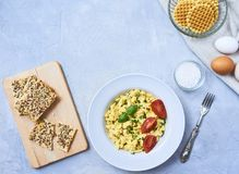 Scrambled eggs in plate on rustic background royalty free stock image