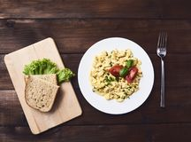 Scrambled eggs in plate on rustic background royalty free stock photo