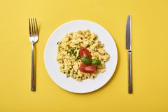 Scrambled eggs in plate on rustic background stock photo