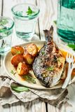 Tasty seabream and potatoes with herbs and tomatoes. On old table stock image
